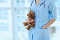 Pediatrician. Cropped image of female pediatrician holding little teddy bear royalty free stock images