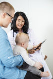 Pediatrician With Digital Tablet Looking At Baby Held By Woman Stock Photography