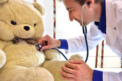 Pediatrician doctor auscultating teddy close up Royalty Free Stock Photos
