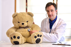 Pediatrician doctor auscultating teddy front position Stock Image