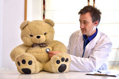 Pediatrician doctor auscultating teddy side position Royalty Free Stock Images