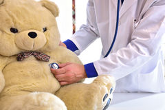 Pediatrician doctor behind table auscultating teddy close up Stock Image