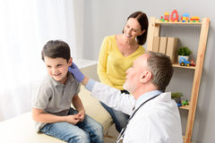 Pediatrician doctor examining child. Everything looking good. Shot of sick little boy being examined by pediatrician with his mother Stock Photos