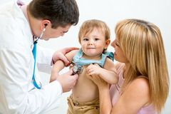 Pediatrician doctor examining child. Mother Stock Images