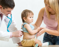 Pediatrician doctor examining child. Mother supporting kid. Stock Image