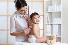 Pediatrician doctor examining heartbeat of baby with stethoscope Royalty Free Stock Photos