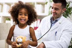 Pediatrician doctor examining kid. Pediatrician doctor examining happy smiling kid Stock Images