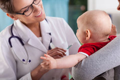 Pediatrician doctor examining little baby Royalty Free Stock Images