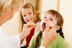 Pediatrician doctor examining throat of girl Royalty Free Stock Images
