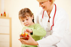 Pediatrician doctor giving candy to little patient Stock Photo