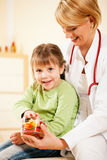 Pediatrician doctor giving candy to little patient Stock Images