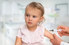 Pediatrician doctor is injecting vaccine to shoulder of baby. Vaccination concept royalty free stock image