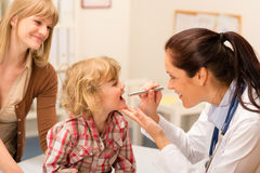 Pediatrician examine child throat look with light. Little girl having throat examination by pediatrician using light pen Stock Photo