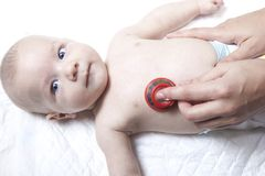 Pediatrician examines newborn baby boy with stethoscope Royalty Free Stock Images