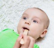 Pediatrician examines a newborn baby with a spatula Stock Photography