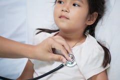 Pediatrician examining asian little girl& x27;s heart royalty free stock photos