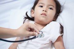 Pediatrician examining asian little girl& x27;s heart stock images