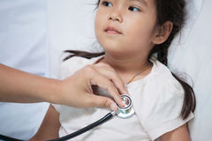 Pediatrician examining asian little girl& x27;s heart Royalty Free Stock Photos