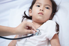 Pediatrician examining asian little girl& x27;s heart Stock Images