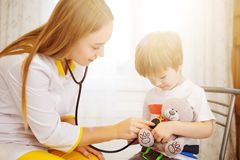 Pediatrician examining baby boy. Doctor using stethoscope to listen to kid and checking heart beat.  royalty free stock photography