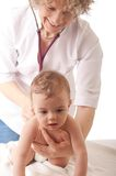 Pediatrician examining baby with stethoscope. Stock Images