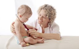 Pediatrician examining baby with stethoscope. Stock Image
