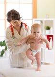 Pediatrician examining cute baby boy. Doctor testing walking reflex Stock Image
