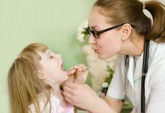 Pediatrician examining girl's throat Royalty Free Stock Image