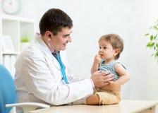 Pediatrician examining heartbeat of baby with Stock Photo