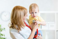 Pediatrician examining heartbeat of baby with Royalty Free Stock Photos