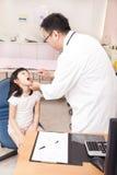 Pediatrician examining  kid throat with  tongue depressor Royalty Free Stock Photo