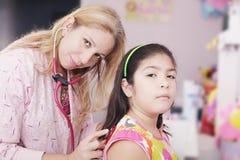 Pediatrician examining little girl Stock Photos