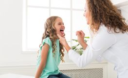 Pediatrician examining little girl`s throat in clinic royalty free stock photo