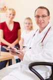 Pediatrician with family in his surgery Stock Photo