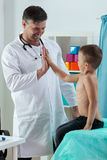 Pediatrician giving boy a five Stock Photography