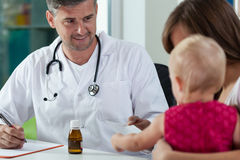 Pediatrician giving little girl a recipe royalty free stock photo