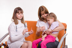 Pediatrician is going to get a shot sick child sitting on hands of mother Stock Photography