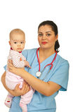 Pediatrician holding baby Stock Images