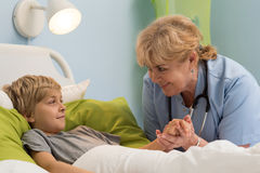 Pediatrician holding hand of her patient Stock Photo