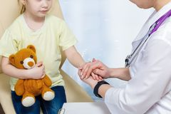 Pediatrician is holding a hand of a small child in protective gesture. A closeup of female pediatrician holding a hand of a small child sitting with a toy bear royalty free stock image