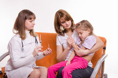 Pediatrician holding a syringe for sick child sitting on hands of mother Royalty Free Stock Image