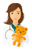 Pediatrician holding teddy bear Stock Images