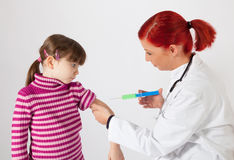 The pediatrician inoculating a small girl Royalty Free Stock Image