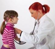 The pediatrician listens on a little girl Stock Photos