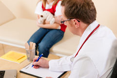 Pediatrician with little patient in his surgery Stock Photo