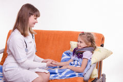 Pediatrician looks at the sick child and keeps his hand Royalty Free Stock Photos