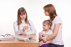 A pediatrician looks at the thermometer, sitting next to a woman with a child on her lap Royalty Free Stock Photography