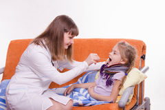 Pediatrician looks at the throat of a sick child Royalty Free Stock Photography