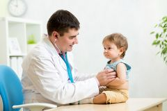 Pediatrician man examining heartbeat of baby boy. Pediatrician men examining heartbeat of kid boy with stethoscope Stock Photography