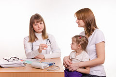 Pediatrician offers to put a thermometer child on the lap of mother Royalty Free Stock Image